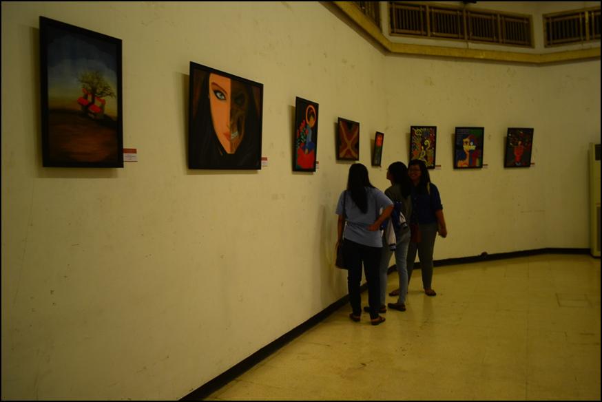 Pengunjung menikmati lukisan yang ada di pameran TITIK AWAL #2 : Kaki Kiri Tangan Kanan.