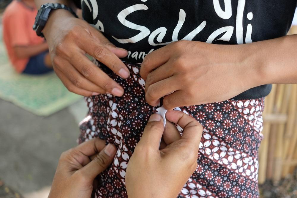 Mengenakan Jarik atau sarung tradisional Jawa.